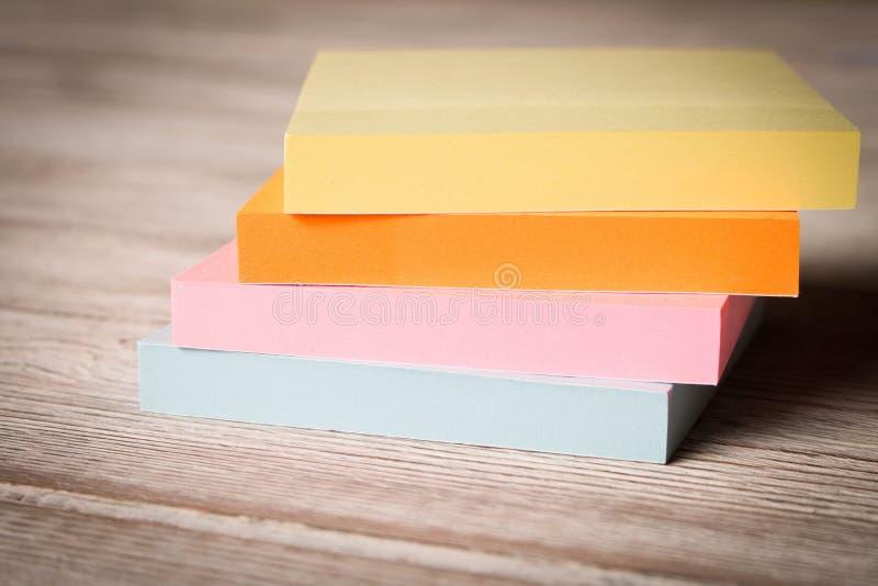 Packar av färgrika klistermärkear för anmärkningar på en trätabell arkivfoton