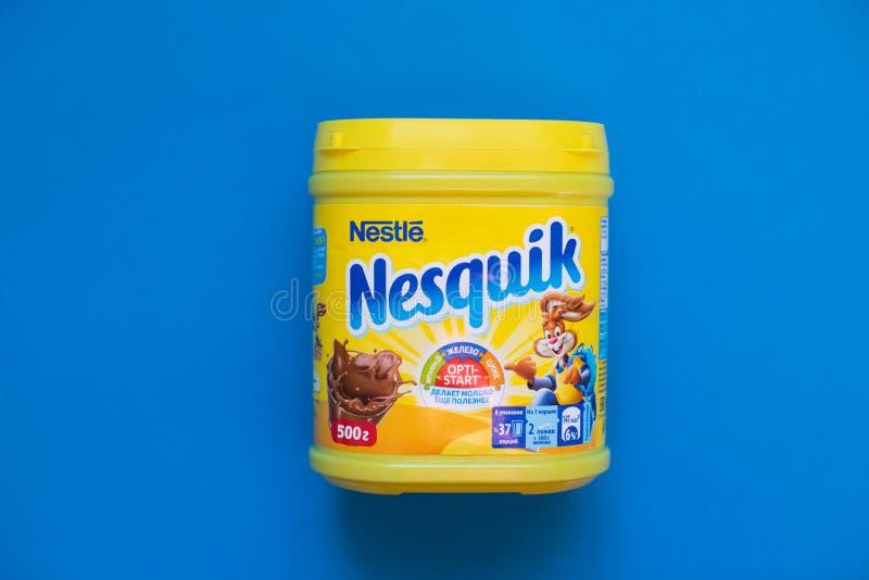 Packe av choklad- och kakaodrinken Nesquik vid Nestle på blå bakgrund royaltyfri fotografi