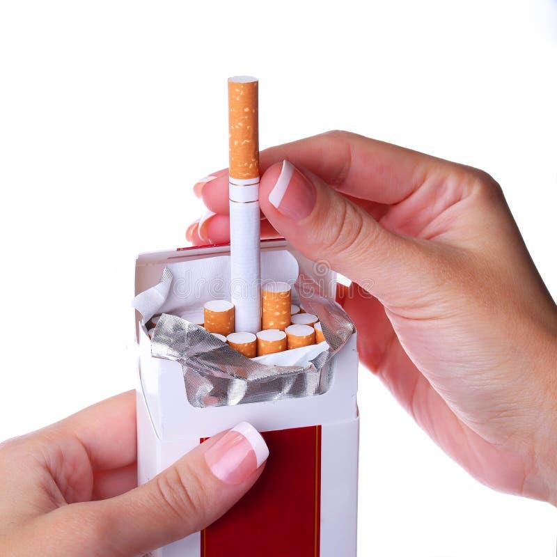 Packe av cigaretter i kvinnlighänder som isoleras på vit arkivfoton