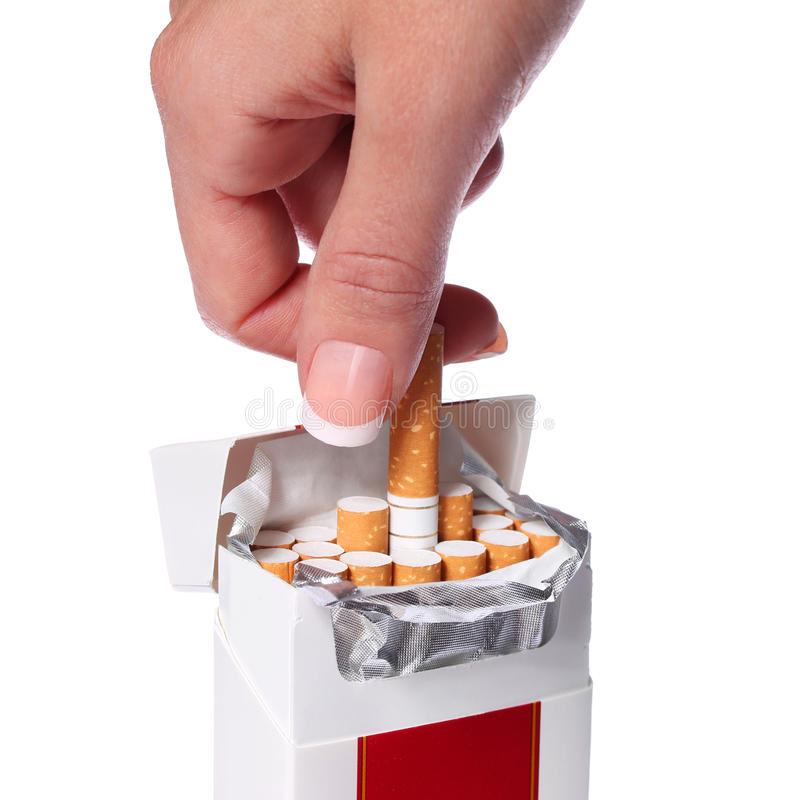 Packe av den isolerade cigaretter och kvinnliga handen royaltyfri foto