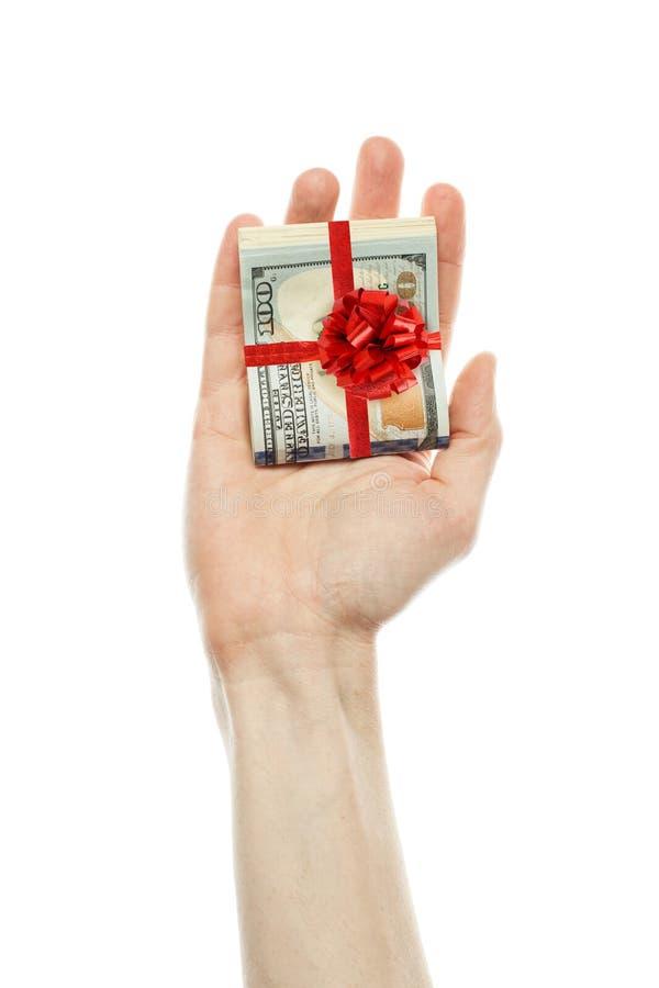 Packe av dollar och det röda bandet Amerikanska dollar kassa med det röda bandet i den manliga handen som isoleras på vit bakgrun royaltyfri bild
