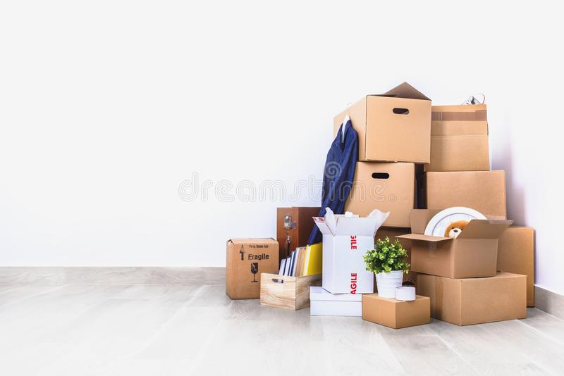 Packed cardboard boxes and stuff during moving into new home stock images