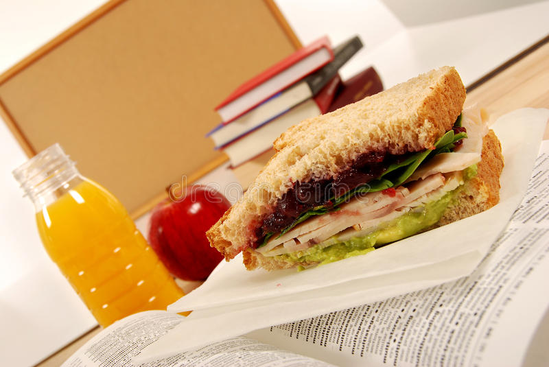 Packed school lunch: turkey sandwich, apple, drink on dictionary book in classroom royalty free stock photo