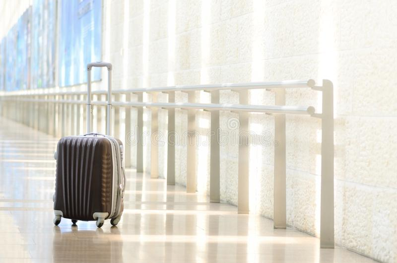 Packed travel suitcase, airport. Summer holiday and vacation concept. Traveler baggage, brown luggage in empty hall. Interior. Copy space stock photography