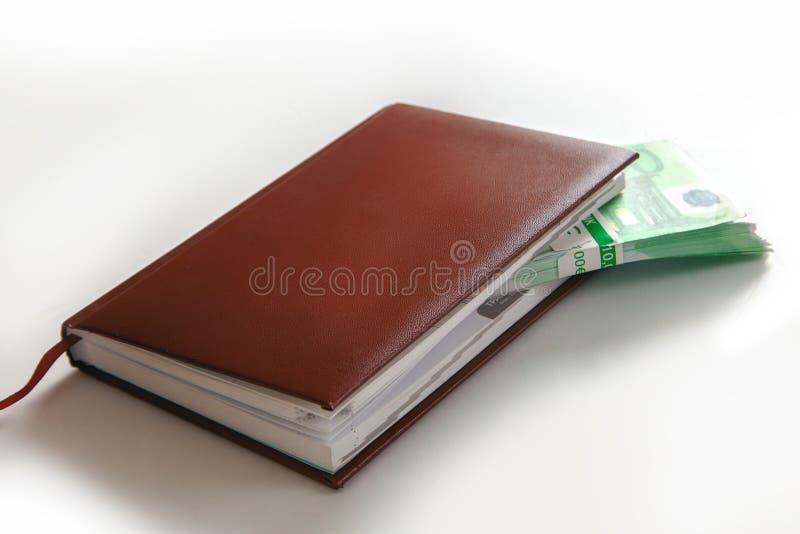 Packen av gröna europengar ligger i en läderanteckningsbok arkivbilder