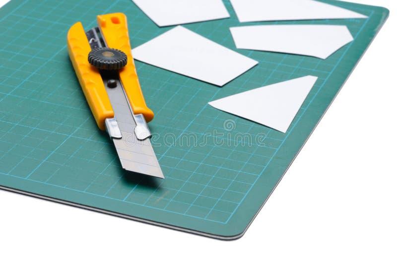 Packen Sie das Schneider-Messer ein, das gerade Weißbuch auf Schneidematte schneidet lizenzfreie stockfotos
