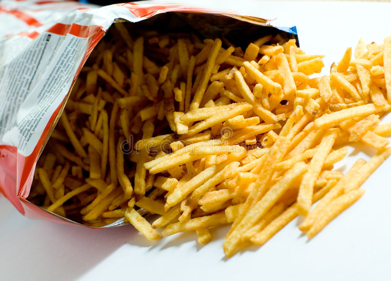 Packet of French Fries. An open packet of French fries with the fries spilling out of the opening onto the table royalty free stock images