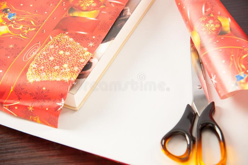 Packing christmas gifts, table with presents during their packing before giving a loved one.  royalty free stock photos