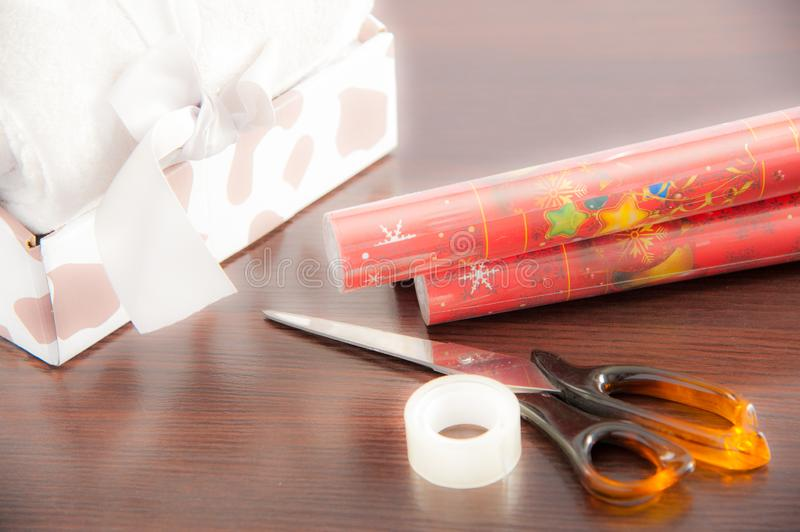 Packing christmas gifts, table with presents during their packing before giving a loved one.  stock images