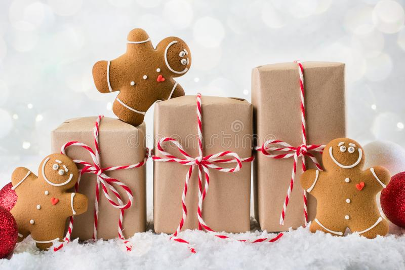 Packing Christmas gifts. Three Christmas gift boxes wrapped in kraft paper tied with red and white string,gingerbread men stock photo