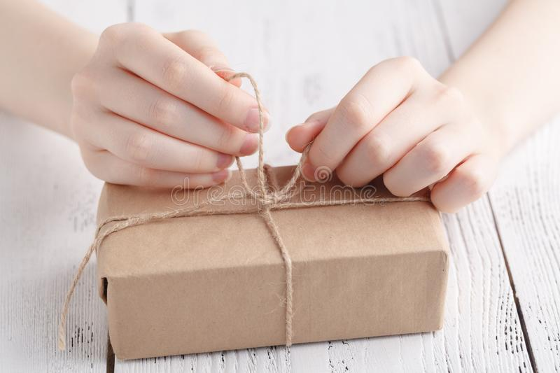 Packing gift in craft papper with twine stock photos