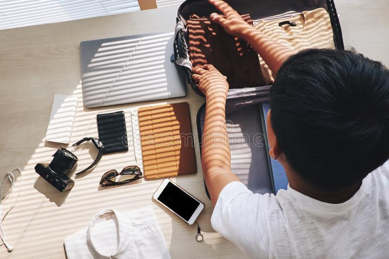 Packing man. Man packing stuff in briefcase for short trip royalty free stock photo