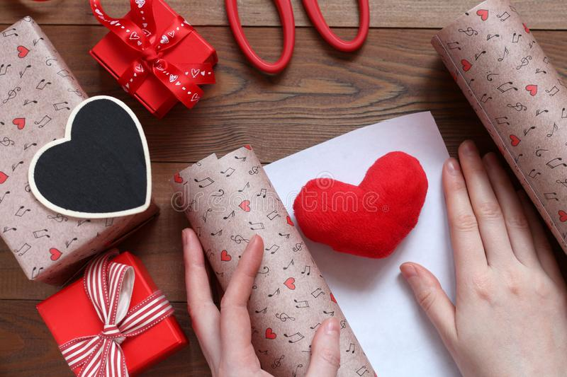 Packing a plush heart in gift paper by St. Valentine`s Day.  stock images