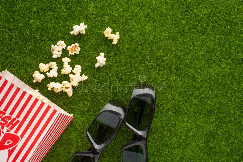 Packing with popcorn on a green lawn with 3D glasses for watching a movie. Grass Watching films about nature. In parks. Recreation royalty free stock photo