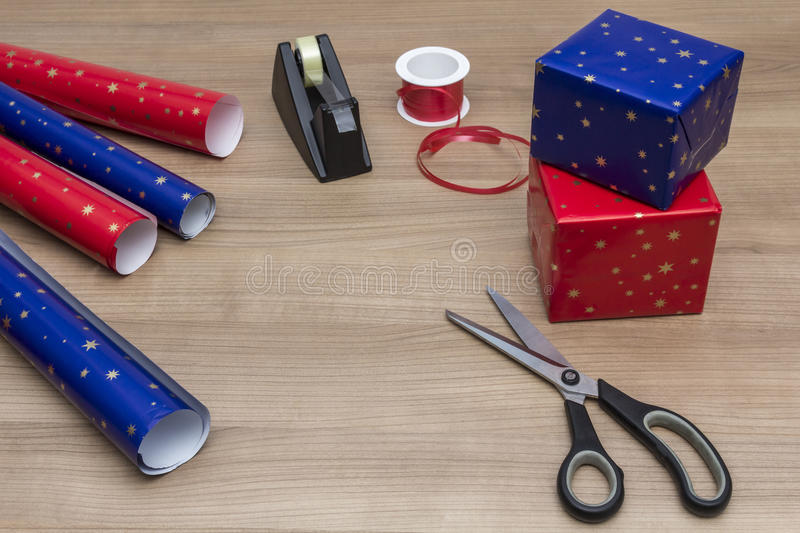 Packing the Presents. All kinds of Equipment for wrapping christmas presents on a wooden table royalty free stock photography