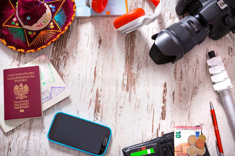 Packing for travel. Travel background with a camera, touristic maps, passport, mobile phone, headphones, wallet with credit cards, euro money, tripod and royalty free stock photos