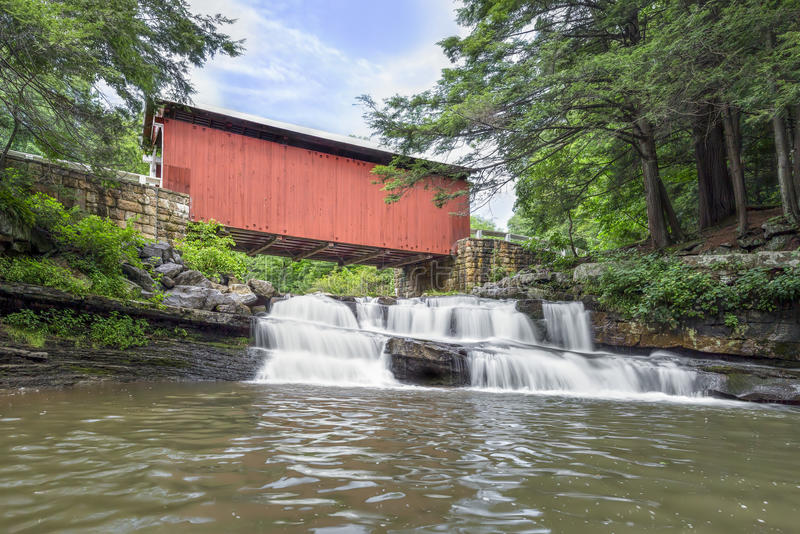 Packsaddle Covered Bridge and Waterfall. Built in 1887, the historic Packsaddle Covered Bridge crosses over a waterfall on Brush Creek in rural Somerset County stock photo