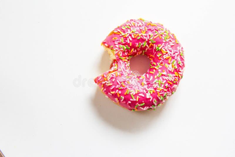 Pacman样式 在白色桌背景的明亮的桃红色可口被咬住的多福饼 免版税库存照片