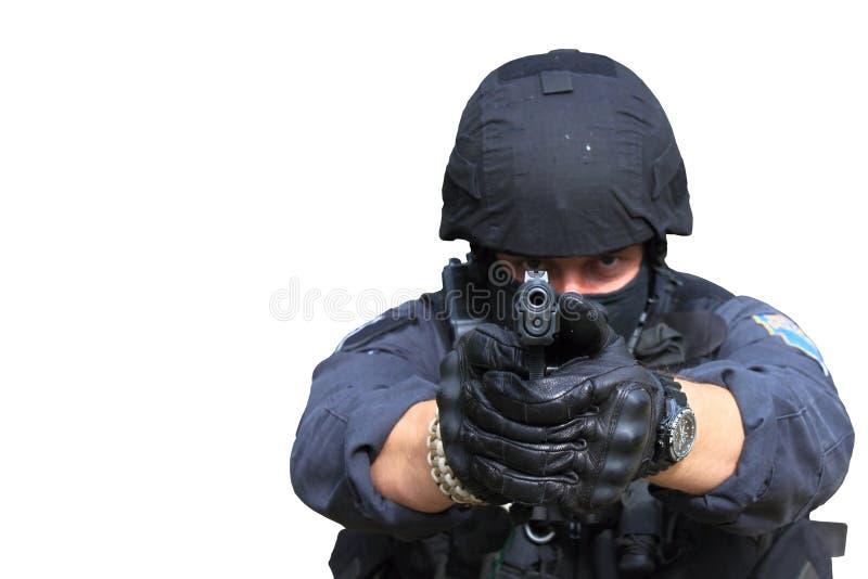 Pacnięcie funkcjonariusz policji wskazuje pistolet przy kamerą, odizolowywającą na bielu zdjęcie royalty free