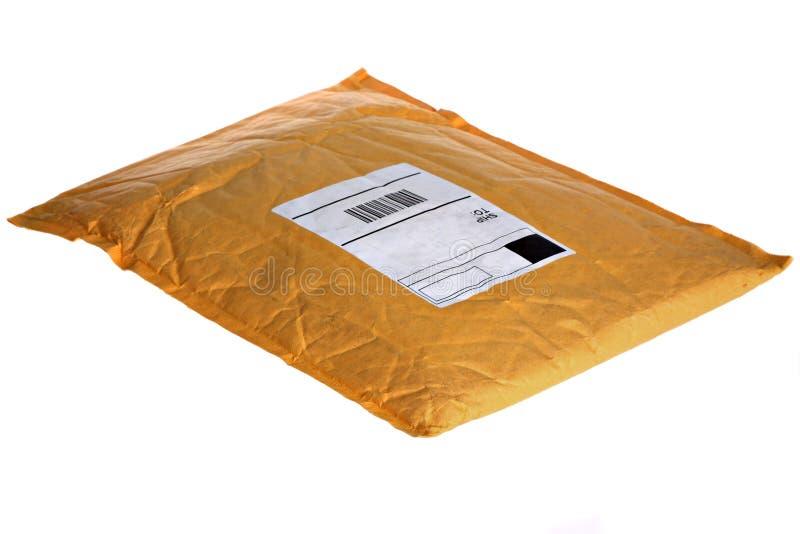 Pacote amarelo empoeirado do correio fotografia de stock