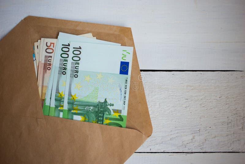 pacote ascendente próximo de cédulas dos Euros do dinheiro no envelope na tabela de madeira foto de stock
