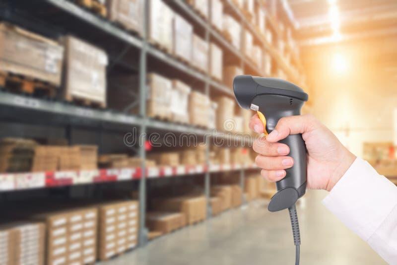 Pacote de verificação e de varredura do trabalhador pelo varredor do código de barras do laser dentro foto de stock