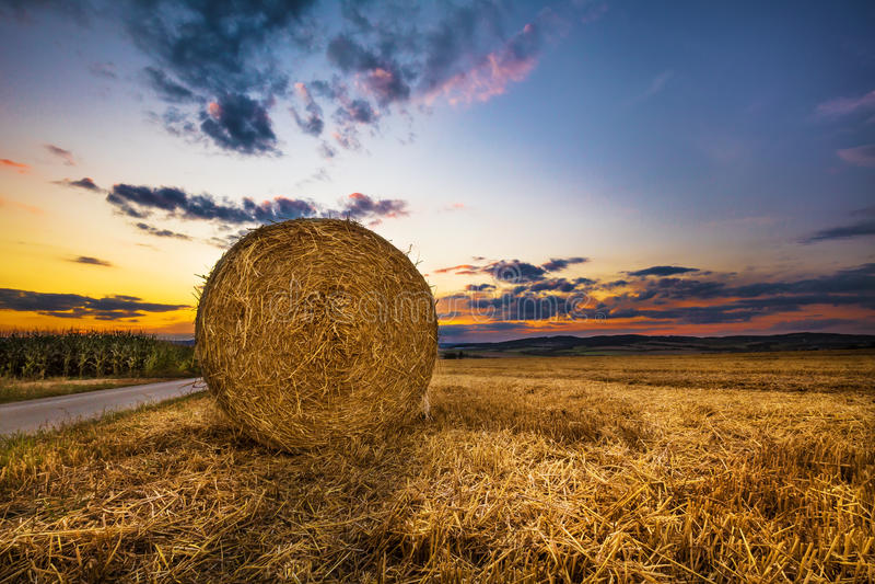 Pacote do feno no campo e no por do sol imagens de stock