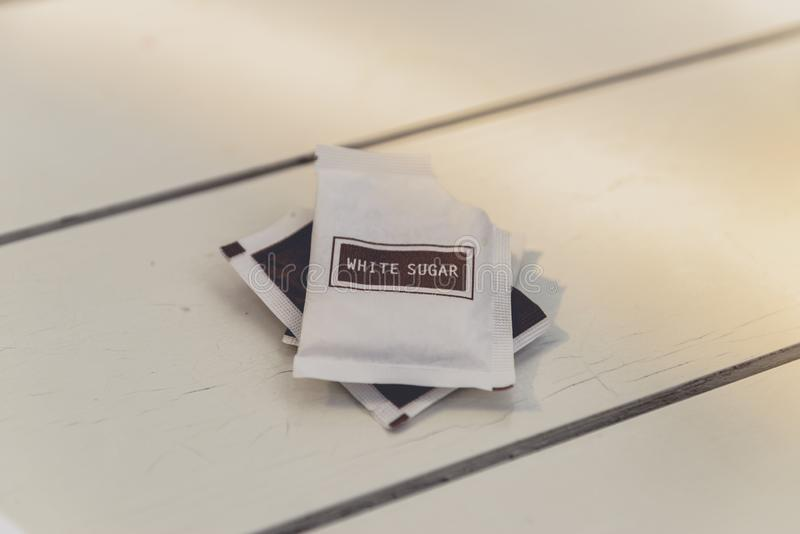 Pacote pequeno do açúcar na tabela de madeira imagem de stock royalty free
