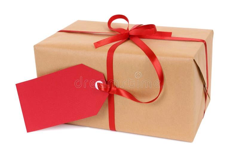 Pacote pequeno ou presente do papel marrom amarrado com a etiqueta vermelha da fita e do presente isolada no fundo branco fotos de stock