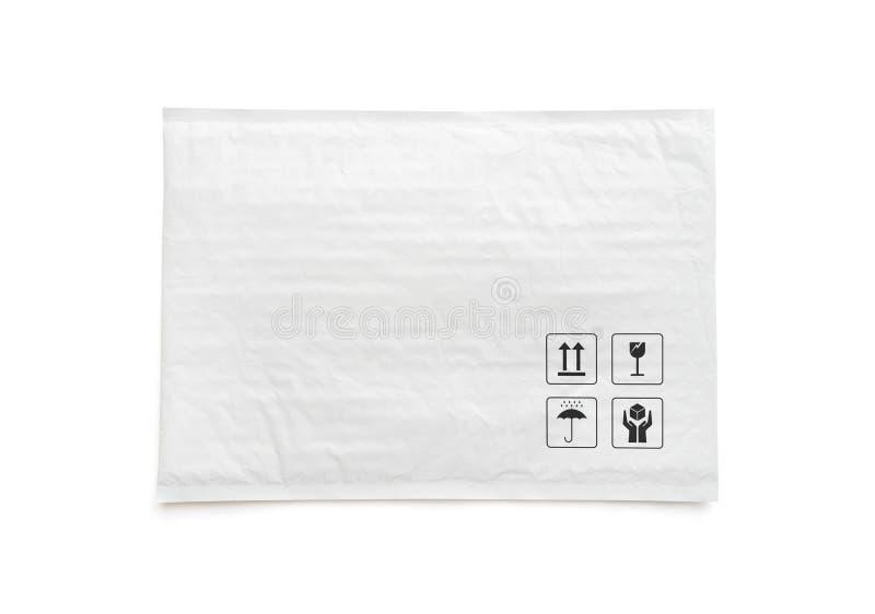 Pacote postal branco Pacote plástico com sinal e símbolo frágeis do cuidado Objeto isolado no fundo branco imagem de stock