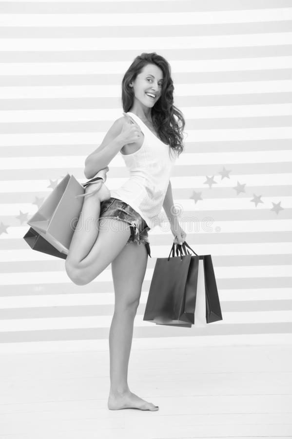 Pacotes demais a guardar somente pela mão A mulher leva o fundo listrado sacos de compras do grupo Favorito finalmente comprado fotografia de stock