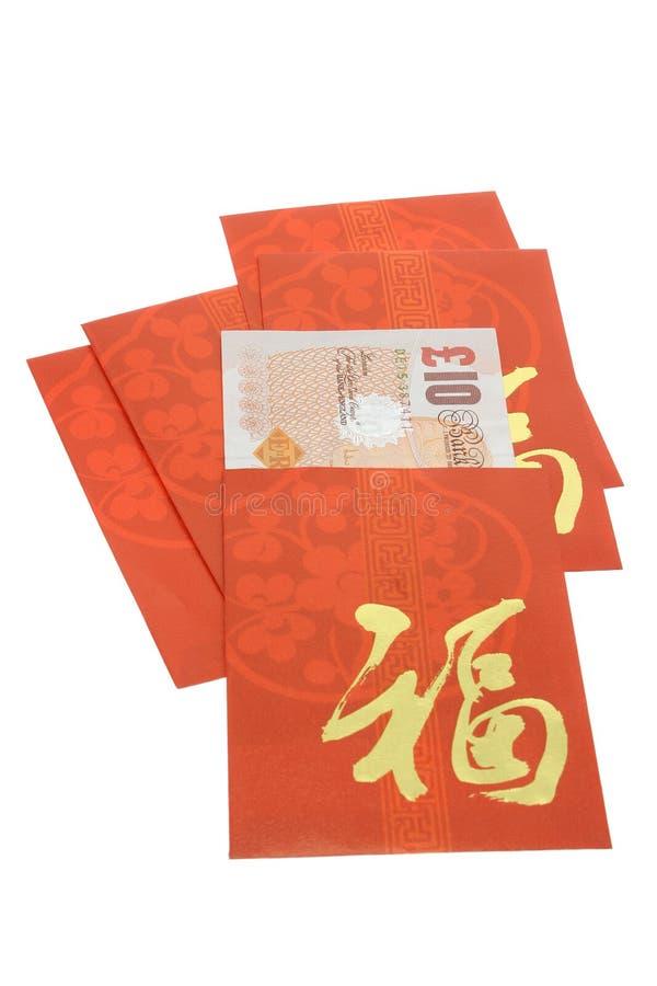Pacotes vermelhos chineses do ano novo e moeda britânica fotos de stock royalty free