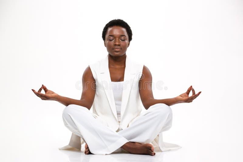 Pacyfikujący ładny afrykański kobiety obsiadanie i medytować w lotos pozie fotografia stock