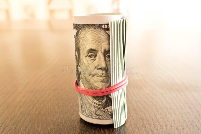 Paczka kręceni 100 dolarowych rachunków Na drewnianym stole z bliska zdjęcie royalty free