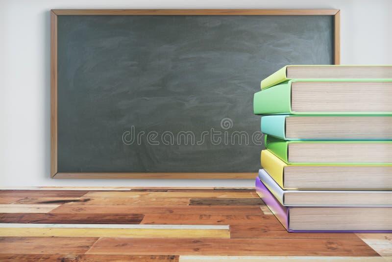 Paczka książki na drewnianym szkolnym biurku z blackboard na bielu obraz royalty free
