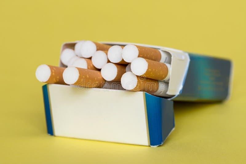 Paczka papierosy na żółtym tle zdjęcia royalty free