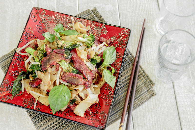 Pad Ki Mao. With char siu pork, broccoli, noodles and bean sprouts, served with Thai basil stock images