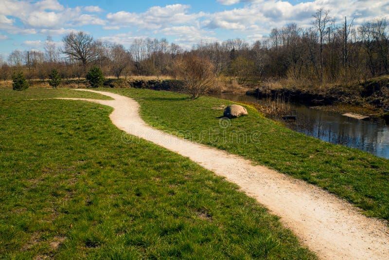 Pad langs de rivier in het voorjaar, omwenteld naar links royalty-vrije stock foto's