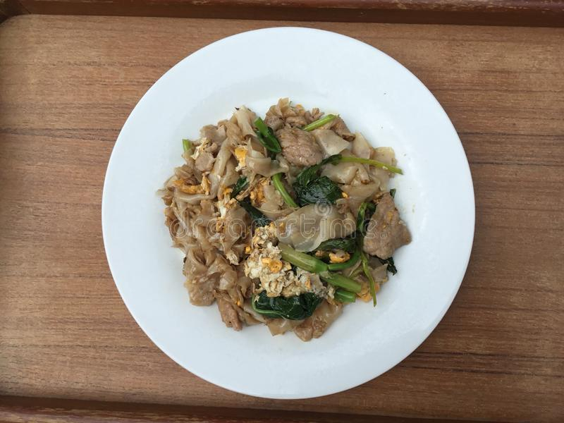 Pad See Eww. Thai food, pad see ew , broad rice noodle stir fried soy sauce,egg, pork meat, chinese broccoli, in a white plate with wood background stock photography