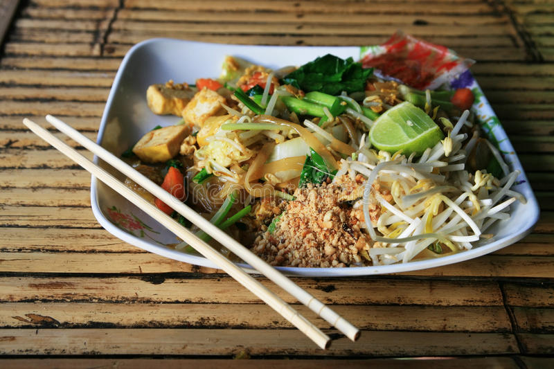 Pad Thai. A plate of pad thai on a bamboo table in Thailand royalty free stock image