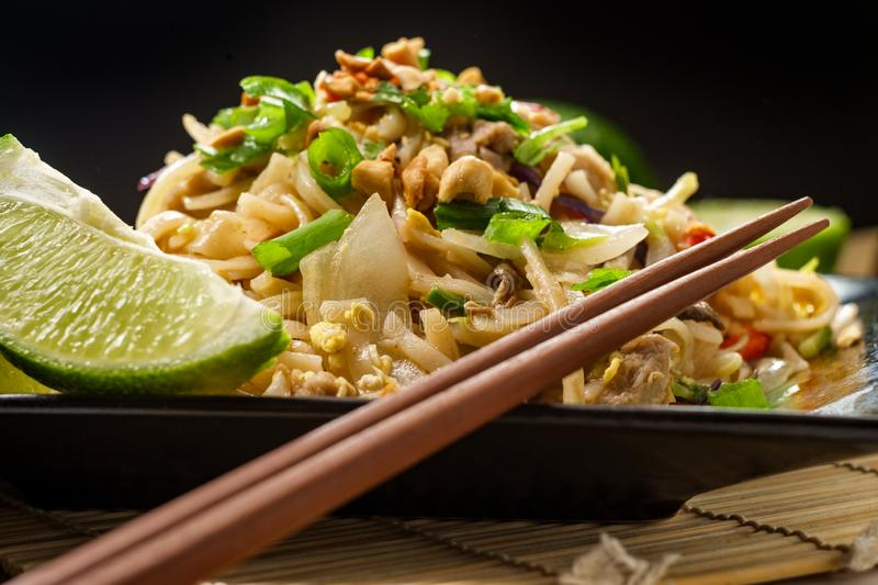 Pad Thai Chicken. Authentic cuisine pad thai with chicken rice noodles red bell peppers bean sprouts and lime garnish royalty free stock images