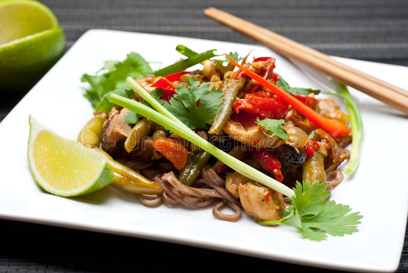 Pad Thai. With chicken and buckwheat noodles on white plate with chopsticks stock images