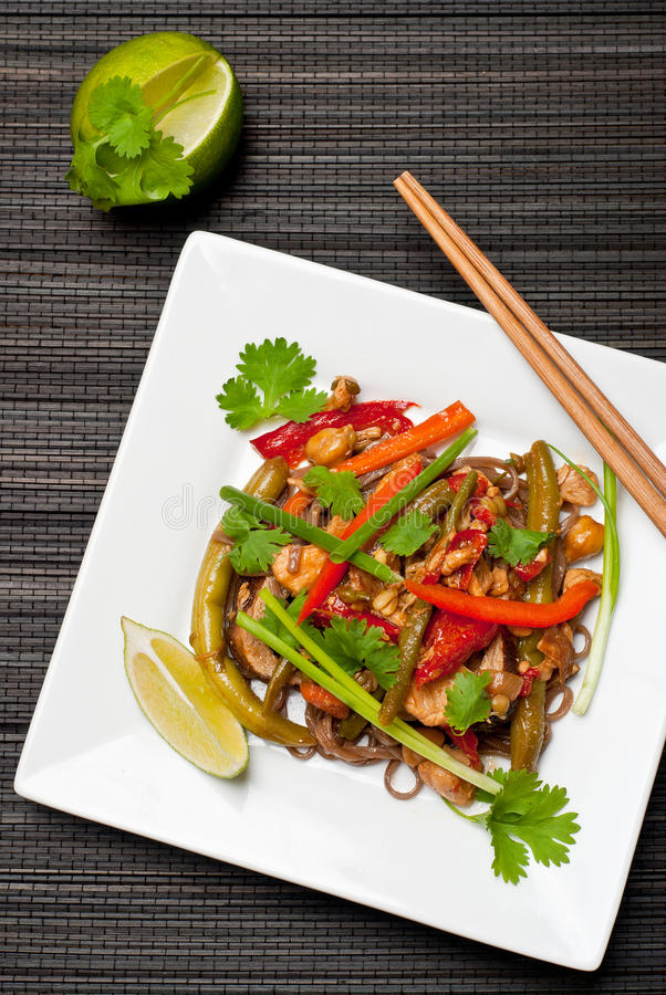 Pad Thai. With chicken and buckwheat noodles on white plate with chopsticks royalty free stock photo