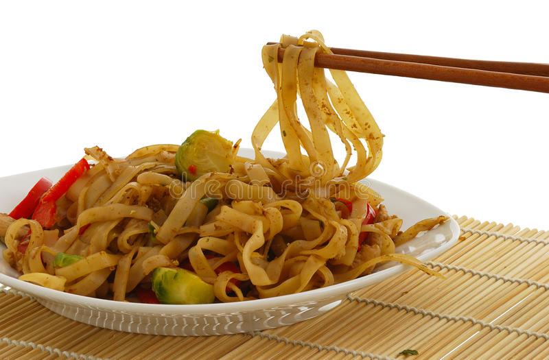 Pad Thai dish on straw pad with chopsticks royalty free stock image