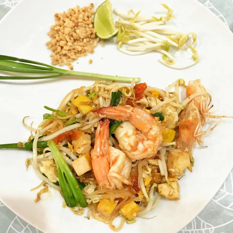 Pad Thai famous Thai dish fried rice noodles with shrimp on white plate. Pad Thai - famous Thai dish fried rice noodles with shrimp on white plate stock photography