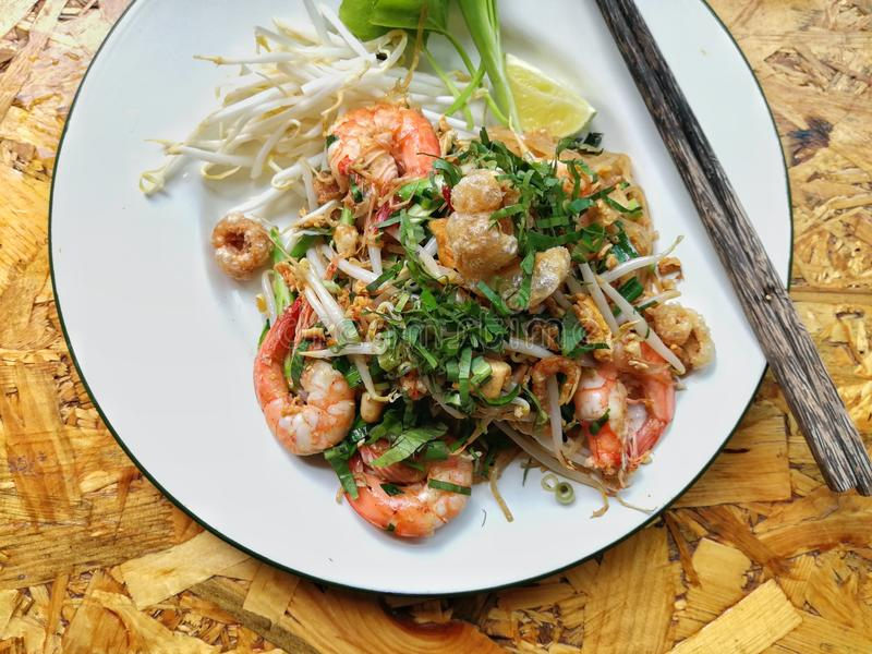 Pad Thai Goong Sod. Fried Rice Sticks with Shrimp on white plate with chopsticks stock photography