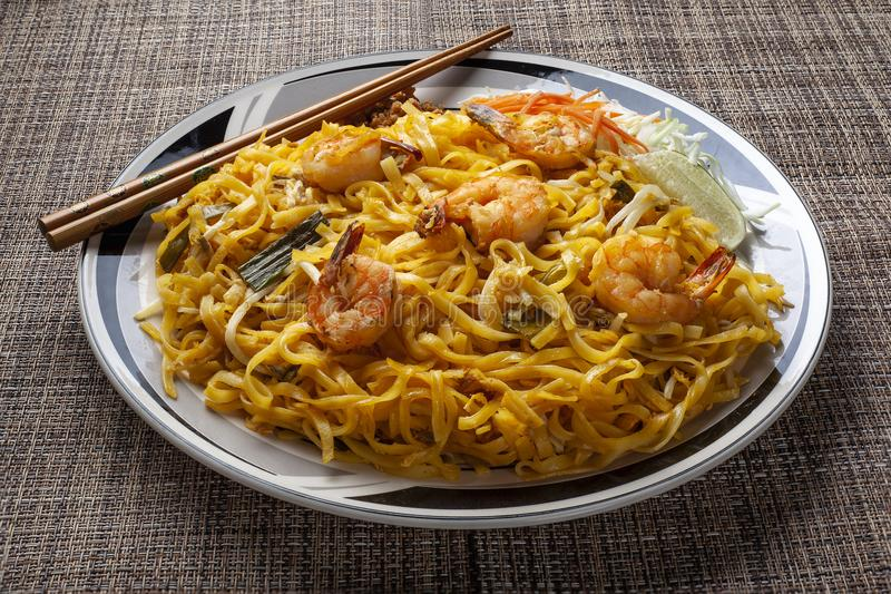Pad Thai Noodles on a Plate with Chopsticks. Delicious stir fried noodles called pad thai in thailand is a tasty dish. It is made with seafood such as shrimp or royalty free stock photo