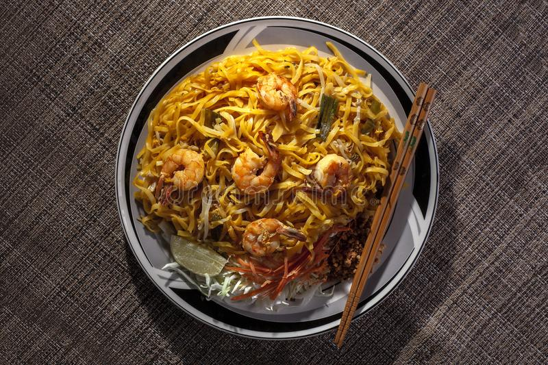 Pad Thai Noodles on a Plate with Chopsticks. Delicious stir fried noodles called pad thai in thailand is a tasty dish. It is made with seafood such as shrimp or stock photography