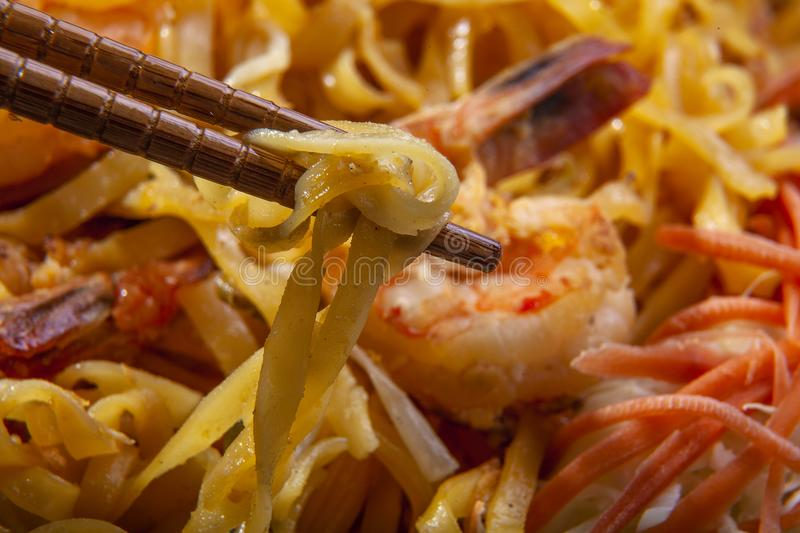 Pad Thai Noodles on a Plate with Chopsticks. Delicious stir fried noodles called pad thai in thailand is a tasty dish. It is made with seafood such as shrimp or stock photos