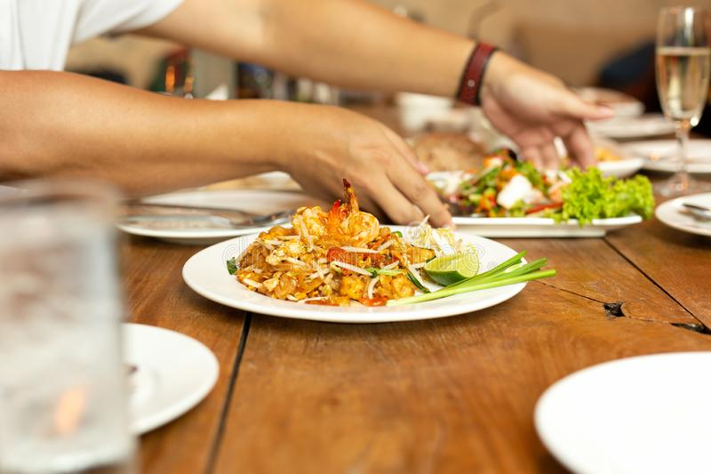 Pad Thai noodles with shrimp on whit plate on wooden table in restaurant. Pad Thai noodles with shrimp on whit plate on wooden table in restaurant stock images
